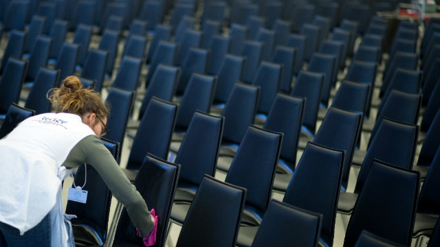 A woman cleans the chairs in the main hall at the congress center.