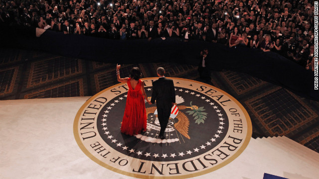 The Obamas walk on stage for their first dance together.