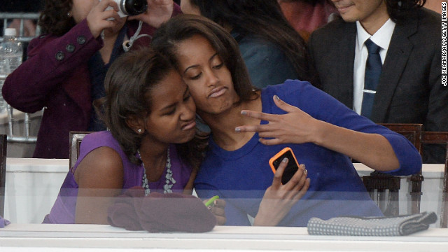 Sasha, left, and Malia Obama take a photo of themselves during the inaugural parade.