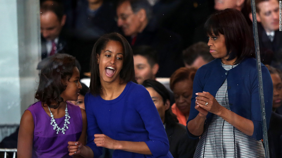 Malia Obama, center, dances on the reviewing stand while her sister Sasha Obama and first lady Michelle Obama look on as the the presidential inaugural parade winds through the nation's capital on Monday, January 21, in Washington.