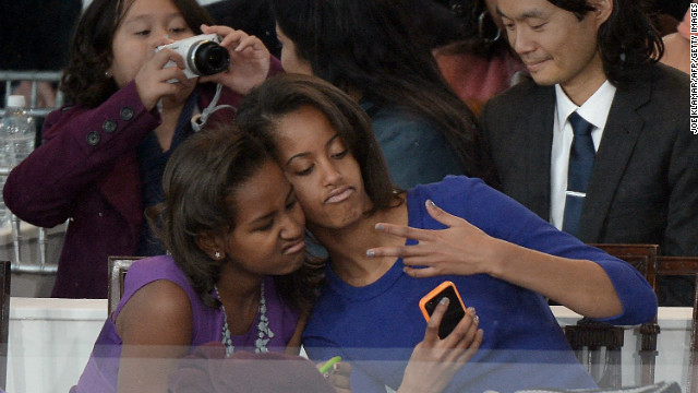 Sasha, left, and Malia take a photo of themselves during Monday's parade.