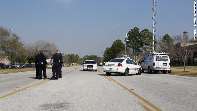 Law enforcement secures the area near Lone Star College. Authorities were searching for a suspect in a wooded area next to the campus, a law enforcement source said.
