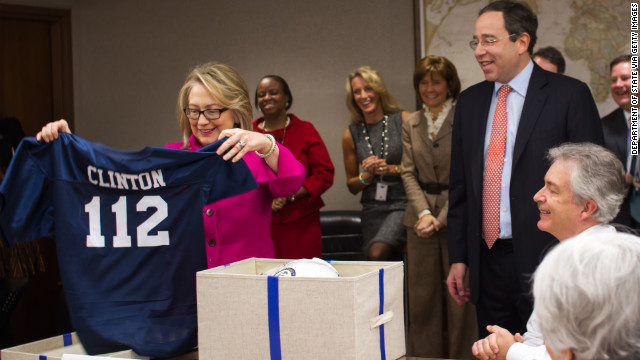 Clinton receives a sports jersey and football helmet from Deputy Secretary Tom Nides, center, after returning to work on January 7, 2013, following a fall where she hit her head and doctors later detected a blood clot. The number 112 represented the number of countries that she had visited as secretary of state.