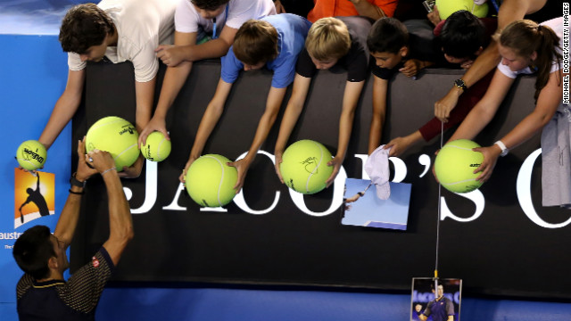 Djokovic signs autographs for fans on January 24.