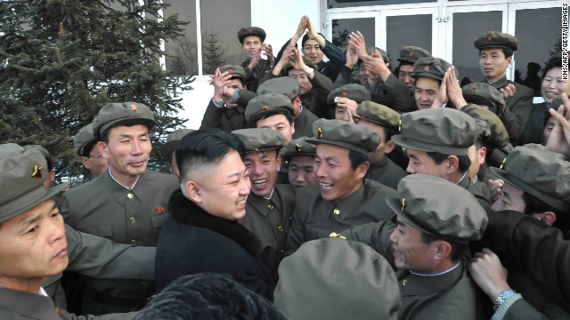 Kim celebrates with staff from the satellite control center in Pyongyang, North Korea, during the launch of a rocket carrying a satellite, in a photo released by the official North Korean news agency on December 12. 