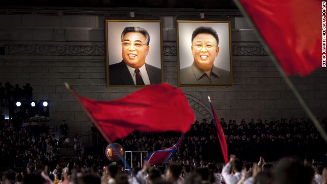 North Koreans wave flags in front of portraits of Kim Il Sung, left, and Kim Jong Il during celebrations to mark the 100th birth anniversary of Kim Il Sung in Pyongyang in April 2012.