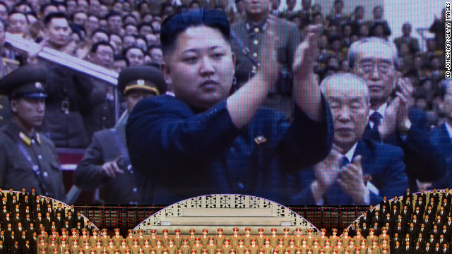 North Korean performers sit below a screen showing images of leader Kim Jong Un in Pyongyang in April 2012.