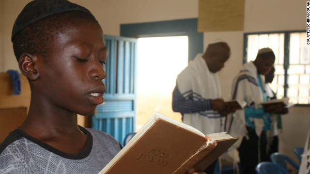14-year-old Kadmiel Izungu Abhor reads from a prayer book wearing his kippah. He says that one day he wants to take a pilgrimage to Israel.
