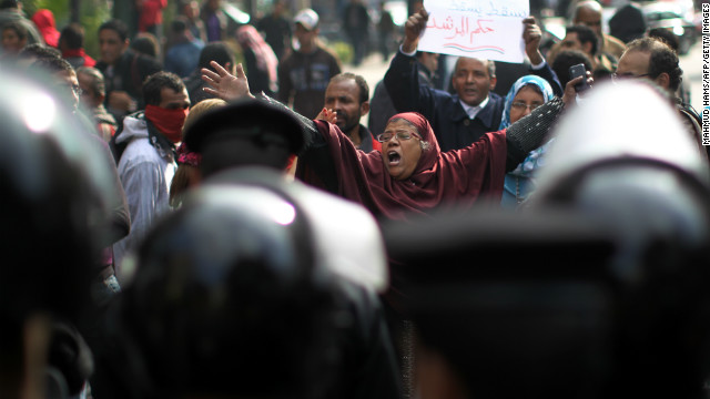 Egyptian riot police stand guard as people protest against Egypt's President Mohamed Morsy in Cairo on December 29, 2012.