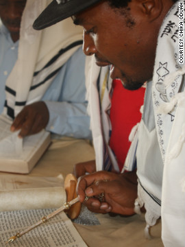 A prayer leader at a synagogue near Abuja reads from the Torah.