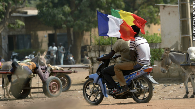 Motocyclists fly French flags alongside their nation's in Markala, Mali.