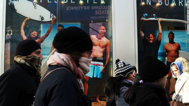 A surfer store with guys in swimwear seems an especially cruel sight for these bundled-up New Yorkers on Tuesday, January 22, as frigid temps hit the region.