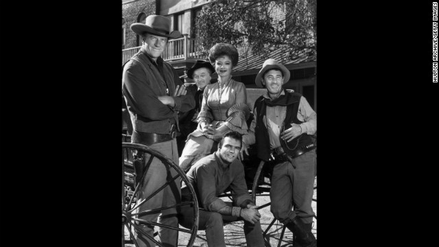 The cast of &quot;Gunsmoke&quot; poses around a wagon in 1962. From left to right: James Arness, Milburn Stone, Amanda Blake, Ken Curtis and Burt Reynolds (seated). 