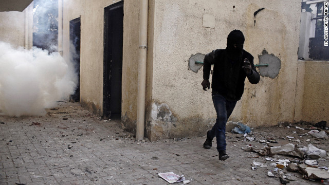 An Egyptian protester runs away from a cloud of tear gas fired by Egyptian riot police on January 26, in Cairo. 