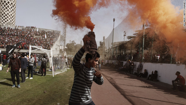 An &quot;Ahly-Ultra&quot; soccer fan holds a smoke flare above his head in Cairo.