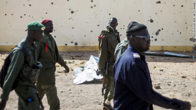 Malian soldiers walk past the bullet-riddled wall of a house in Konna on Saturday, January 26.
