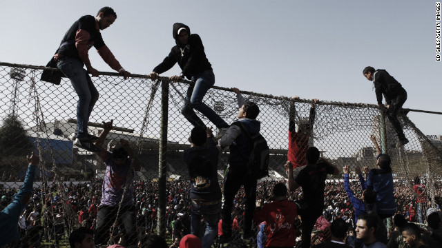 Egyptians climb over a fence at the Al-Ahly home stadium on January 26 in Cairo.