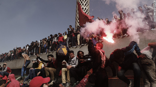 An Al-Ahly soccer fan swings a live flare above his head on January 26 in Cairo.