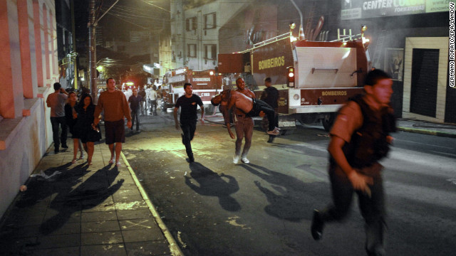 A firefighter, center, carries a victim away from the blaze.