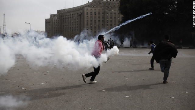 A protester throws a tear gas canister toward riot police in Cairo's Tahrir Square on Sunday, January 27.