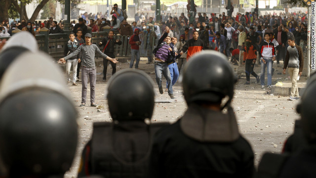 Egyptian protesters throw stones toward riot police on January 27 in Tahrir Square.