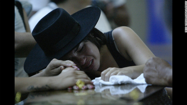 A woman weeps on a coffin as relatives of the nightclub fire victims identify bodies.