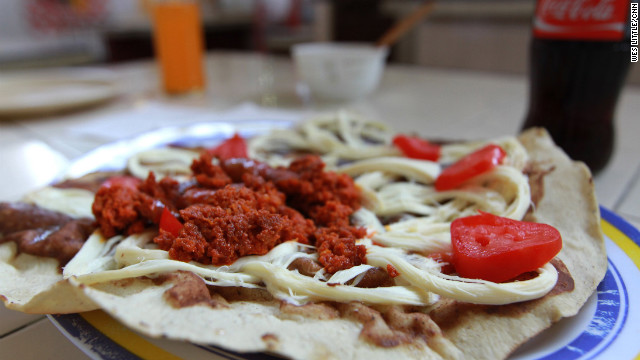 Tlayudas are a Oaxacan specialty, an open-face crisped tortilla with toppings such as beans, cheese, tomatoes and chorizo.