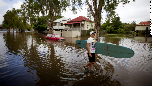 Roger Barnes rescues a friend's surfboard from a flooded home in the inner Brisbane suburb of Newmarket in Queensland on Monday, January 28. 