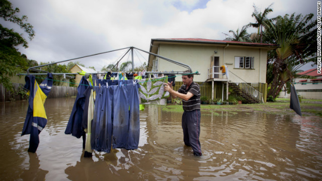 Tony Hall stands in floodwaters as he checks his washing on a clothesline on January 28 in Newmarket.