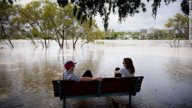 Peter Wison, left, and Beata Jaremko sit on a bench surrounded by floodwaters after the Brisbane River broke its banks on January 28.