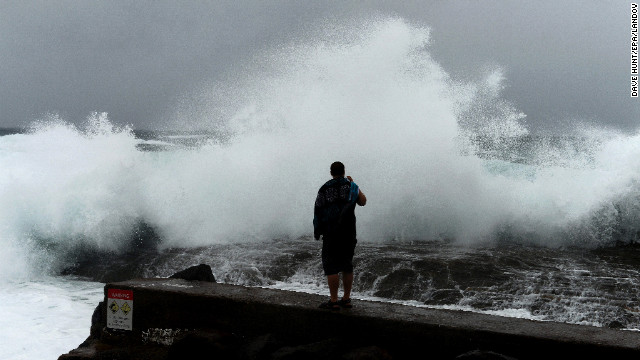 A man films large waves battering the coast on Sunday, January 27, at Snapper Rocks in Coolangatta on the Queensland and New South Wales border.