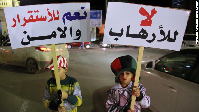Children in Benghazi hold up placards reading