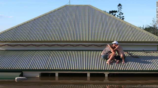 A man comforts his daughter on the roof of their flooded house in Bundaberg on January 29. More than 2,000 homes have been inundated with water in the town, the mayor said.