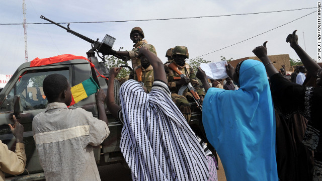 People cheer along a road in Ansongo, a town near the northern Malian city of Gao, as troops from neighboring Niger enter the city.