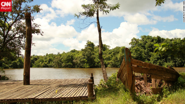 An abandoned boat sits amongst the trees of Hlawga National Park.