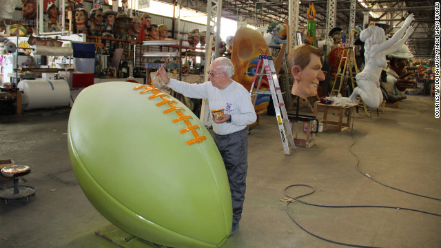 Workers at Mardi Gras World put the finishing touches on football-themed floats.