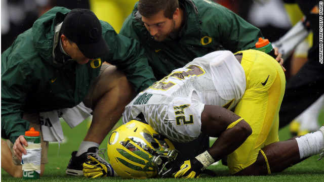 Trainers attend to a University of Oregon player hurt in a football game in Corvallis, Oregon, on November 24, 2012.