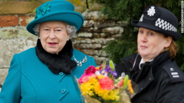 Britain's Queen Elizabeth II hands a police officer some flowers she received from children as she leaves Christmas services at St. Mary Magdalene Church in Sandringham, Norfolk, England.