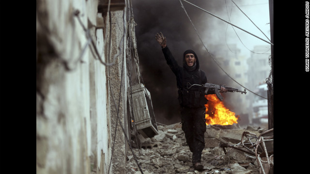 Photographer Goran Tomasevic, embedded with the Free Syrian Army, captured an intense firefight and the death of a rebel fighter in Damascus on Wednesday, January 30. Here, a Free Syrian Army fighter gestures in front of a burning barricade during heavy fighting in the Ain Tarma neighborhood of Damascus.