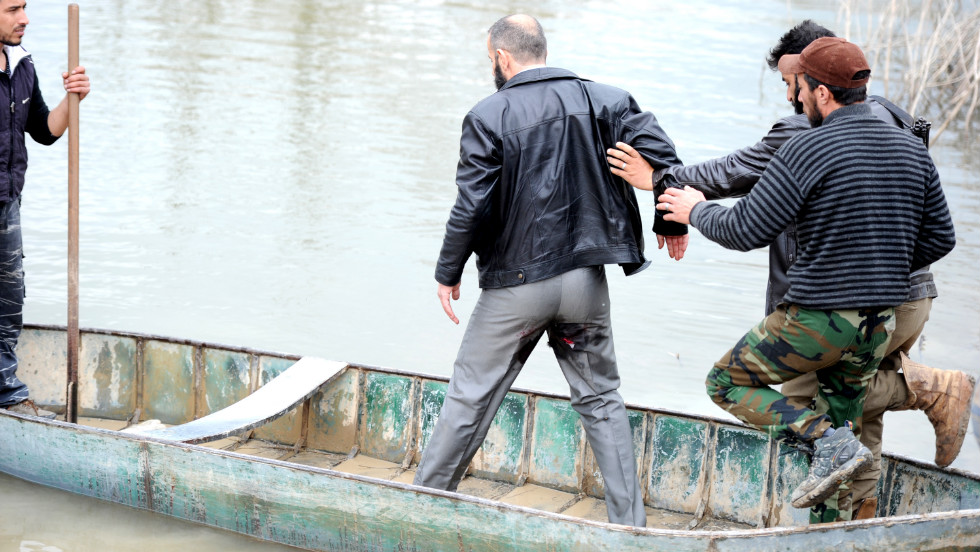 A rebel leader is helped into a boat on Wednesday, January 30, by rebel fighters after he was injured during shelling by pro-Syrian forces. The boat will transport them to Turkey near the northern Syrian town of Darkush. Click through to view images from the Syrian conflict from December and January, or <a href='http://www.cnn.com/2012/12/04/middleeast/gallery/syria-unrest-november/index.html'>see photos from November</a>.