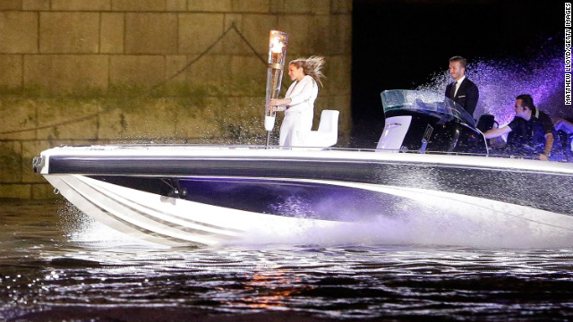 Beckham passes under Tower Bridge in a speedboat which carries the Olympic Torch and its torchbearer in 2012.