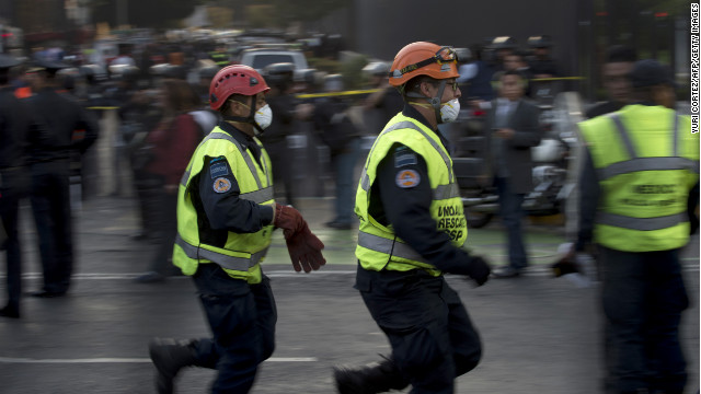 Rescue workers head for the headquarters of state-owned Mexican oil giant Pemex in Mexico City on Thursday.