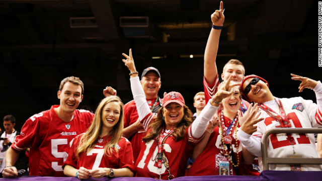 49ers fans cheer for their team from the stands during pre-game warm-ups.