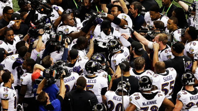 Baltimore Ravens players gather around team leader Ray Lewis as he leads them in a rally on the field just before the start of the game.
