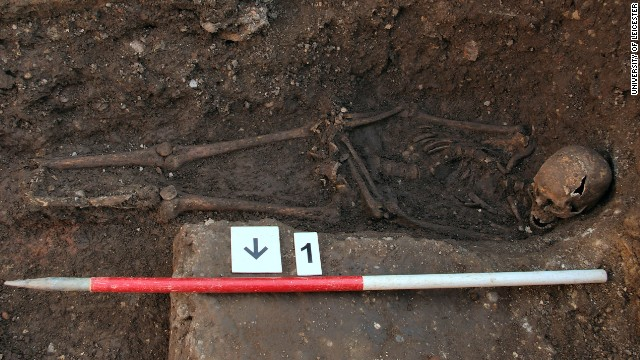 The skeleton being excavated, shows the curve in the spine and the way the head had been squashed into the grave. The hands may also have been tied.