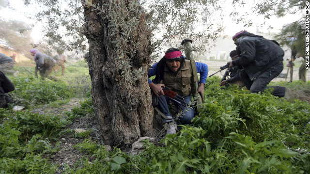 Free Syrian Army fighters run as they enter a Syrian Army base during heavy fighting in the Arabeen neighborhood of Damascus on February 3.