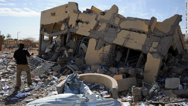 A man searches through the ruins of a building destroyed by French airstrikes in Douentza, Mali, on Tuesday, February 5. The town was retaken by French and Malian troops in January.