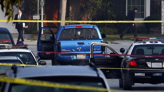 Detectives investigate the scene where officers fired on a vehicle they believed was Christopher Dorner's on February 7, in Torrance, California. Two people in the truck were wounded.