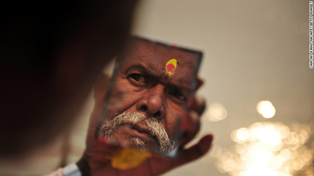 A Sadhu looks in a mirror as he applies paint to his forehead moments after taking a dip in the Ganges river in Allahabad during the beginning of Kumbh Mela in Allahabad on January 13.