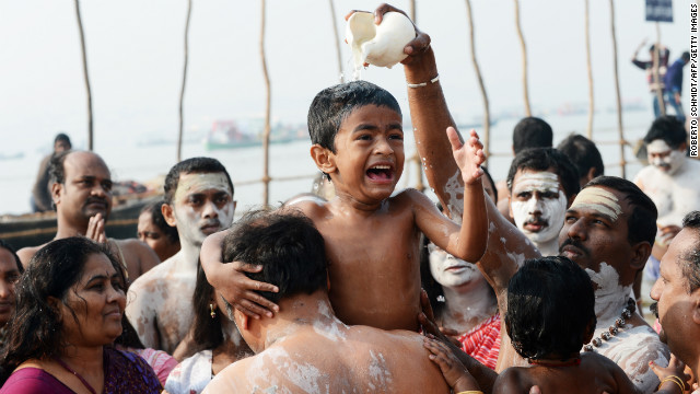 A boy reacts as water is poured over his head at the edge of the Sangam.
